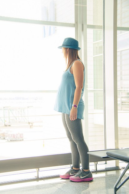 pregnant woman standing in an airport terminal