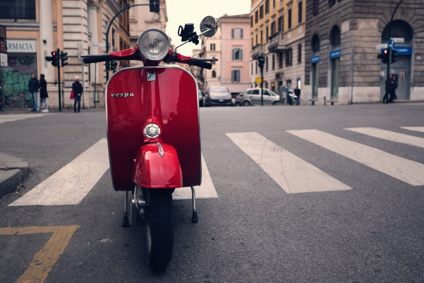 parked red Vespa scooter on Roman street